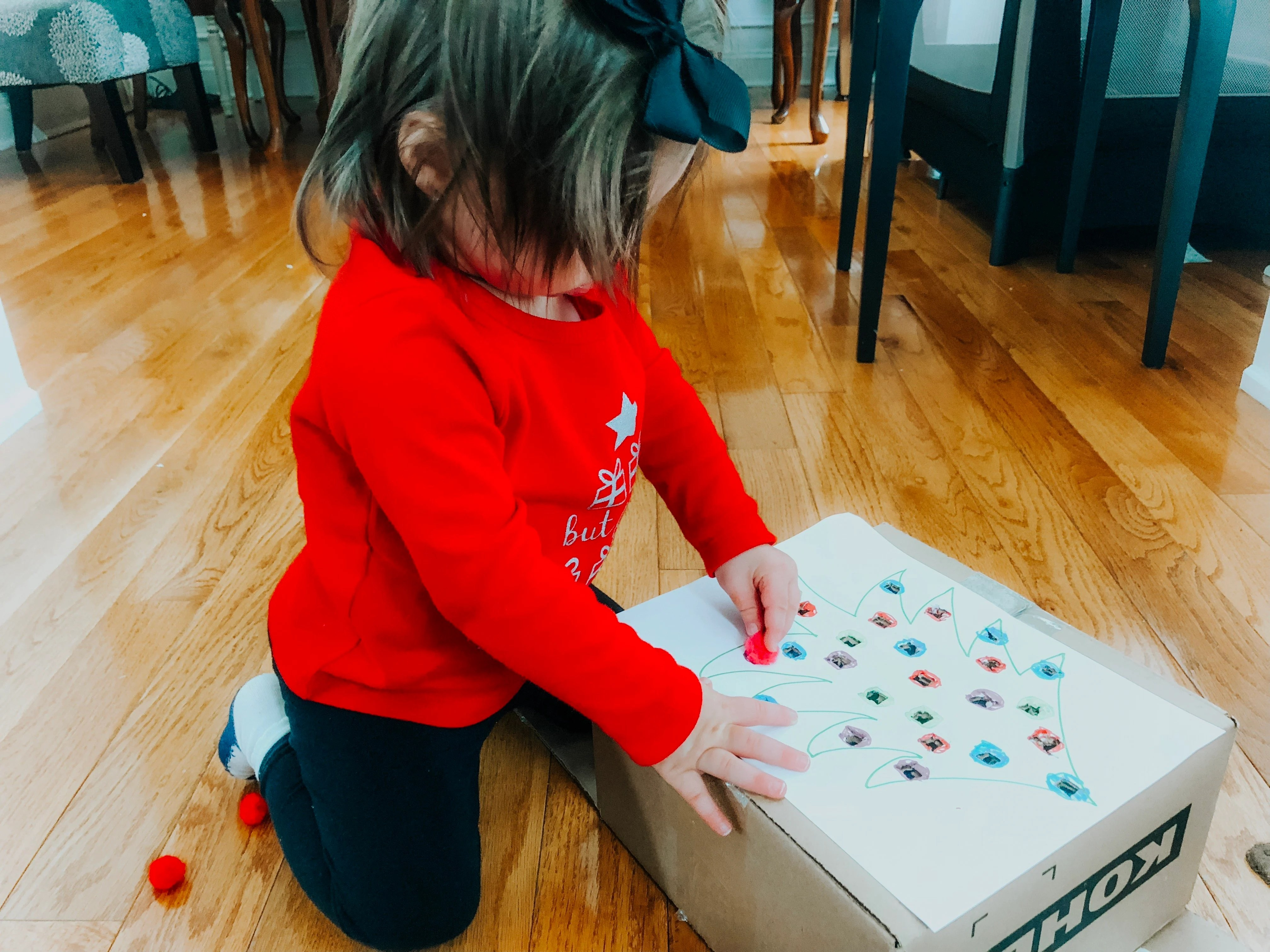 Christmas Pom Pom Push is a fine motor activity for your baby or toddler to help improve their hand and finger skills while doing a fun holiday activity.