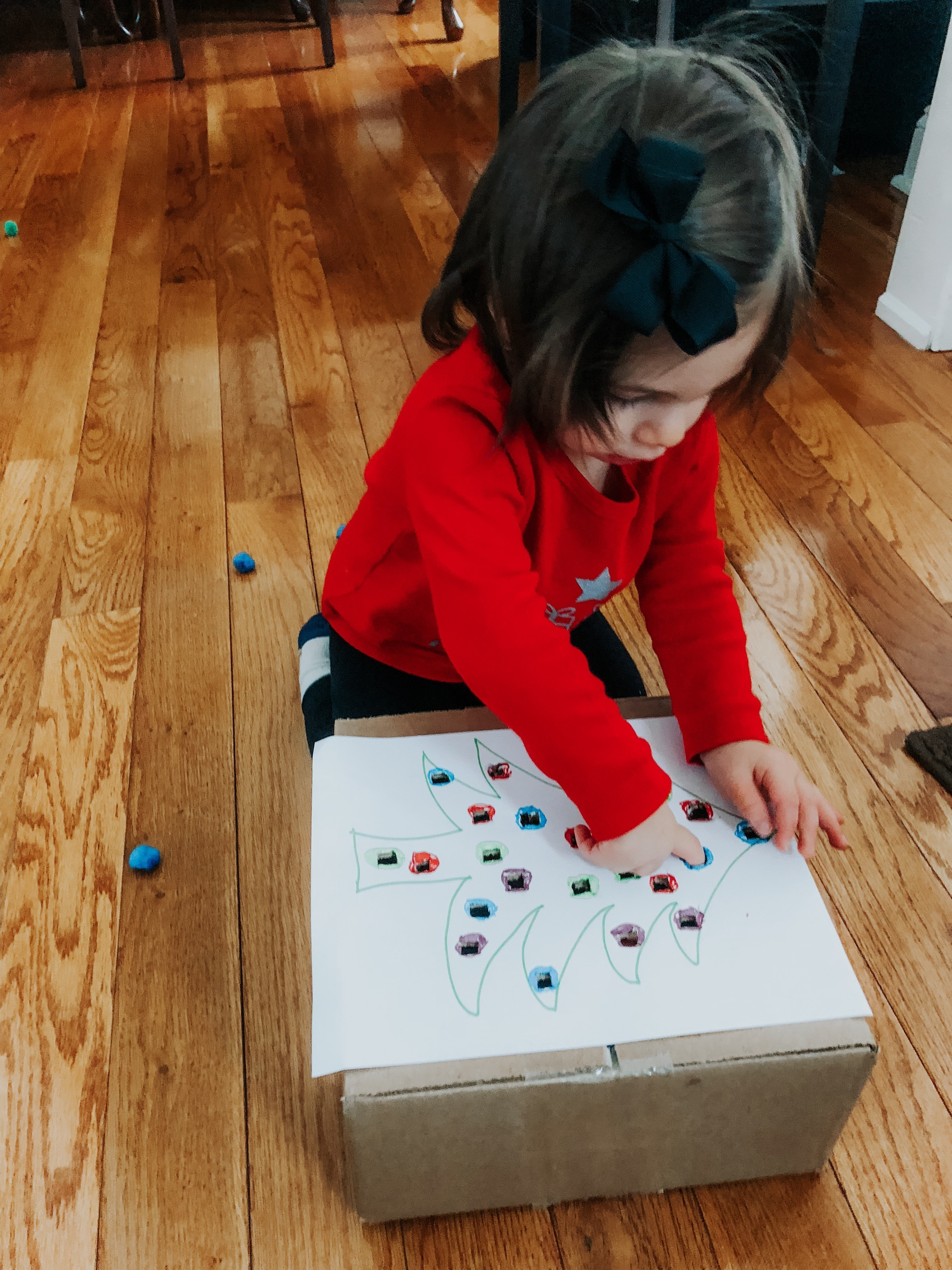 Christmas Pom Pom Push is a fine motor activity for your baby or toddler to help improve hand & finger skills during a fun holiday activity.