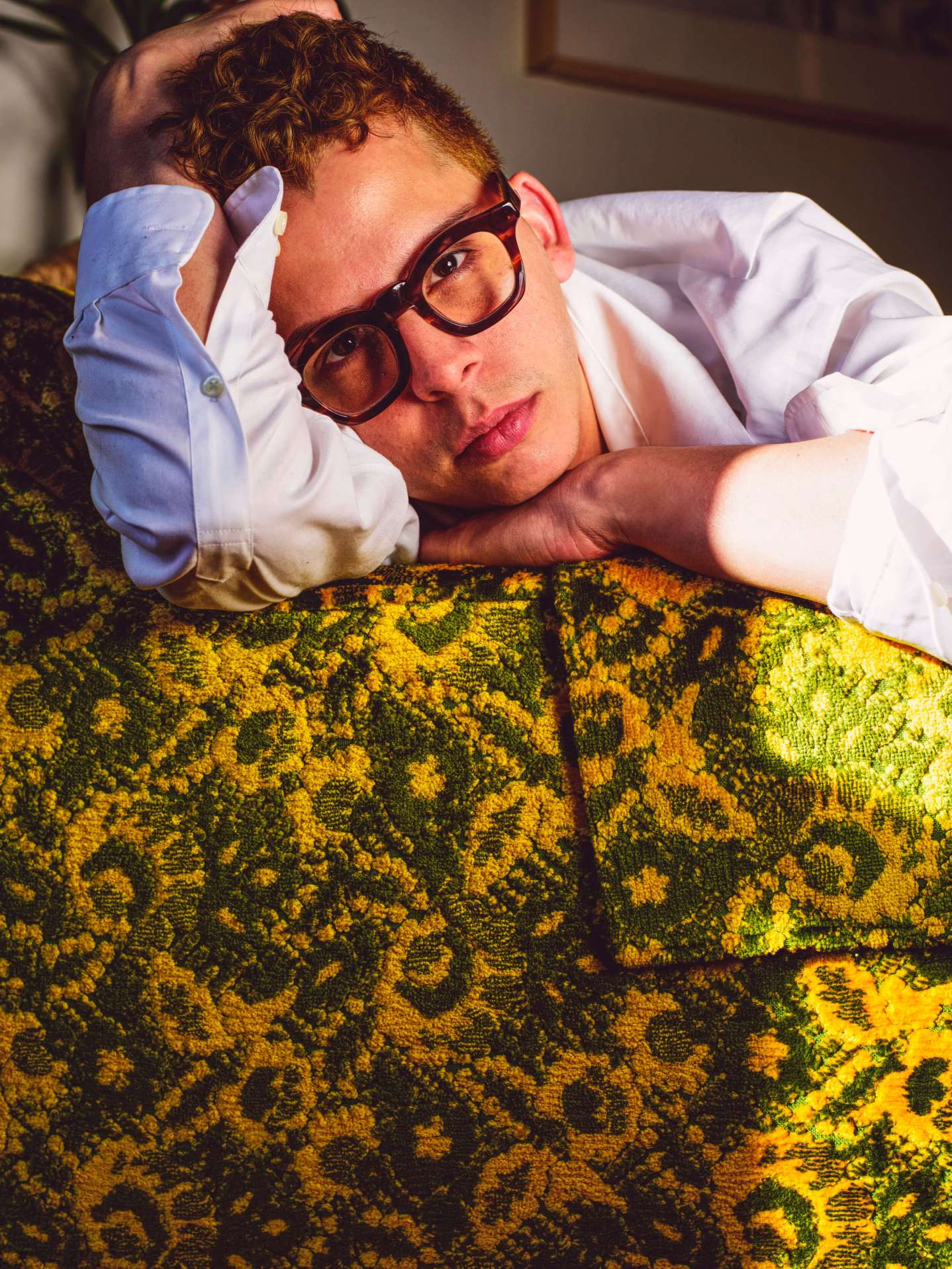human subject resting on yellow and green couch