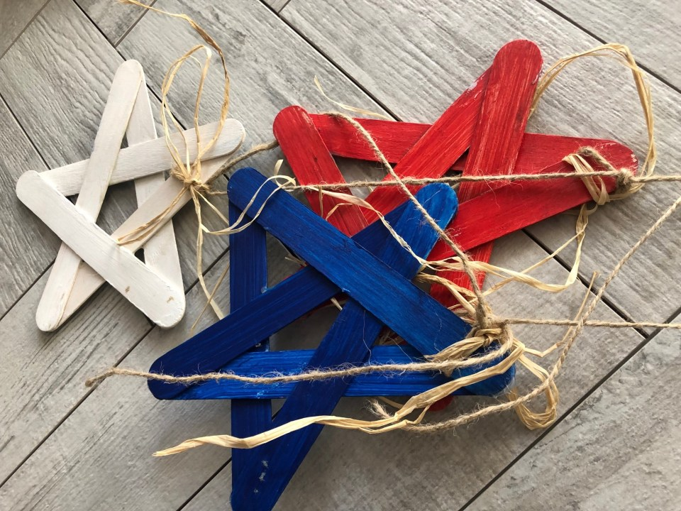 Red White & Blue Star Banner simple DIY project and of course budget friendly to decorate your house or backyard! Paint stir sticks patriotic craft idea