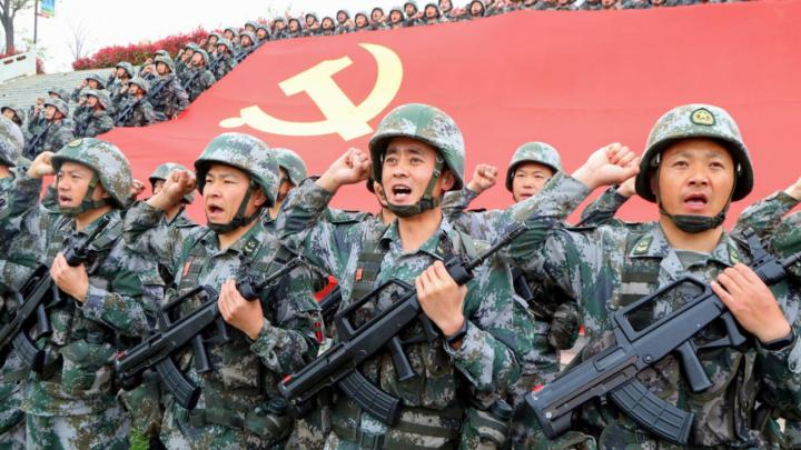 Chinese military in front of party flag