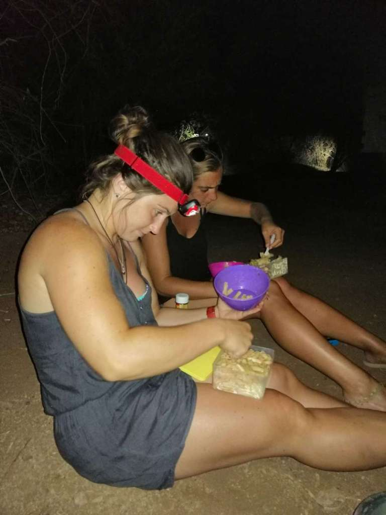 Sitting on the ground to cook pasta by headlamp torch