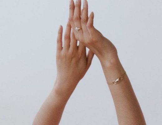 person wearing gold bracelet and gold ring