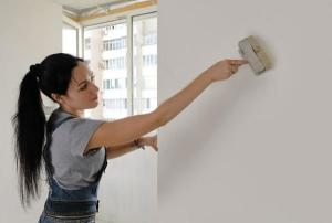 mujer imprimando pared