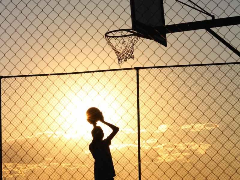 basketball player throwing ball into basketball hoop