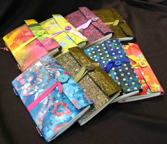 """Travel journals have soft covers. They are 4.5"""" x 6.5"""" in size. Each has a wrap around cover that closes with a ribbon and button."""