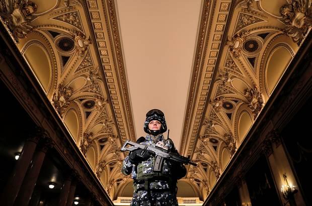 RUMÆNIEN: En kvinde fremviser den nye rumænske militæruniform i Central Army House i Bukarest. Foto: Vadim Ghirda/AP