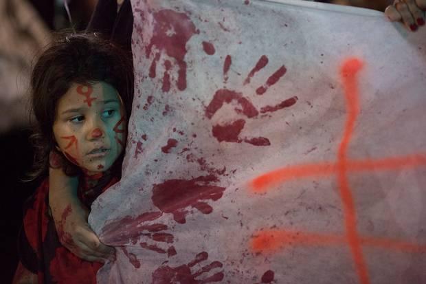 BRASILIEN: I Rio de Janeiro deltager en lille pige i en demonstration imod vold mod kvinder. Foto: Leo Correa/AP