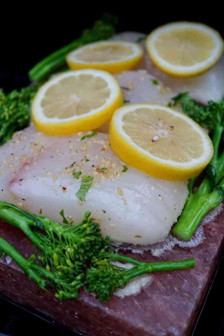 Halibut and broccolini on a salt block with lemons