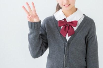 3のジェスチャーをする制服を着た女の子