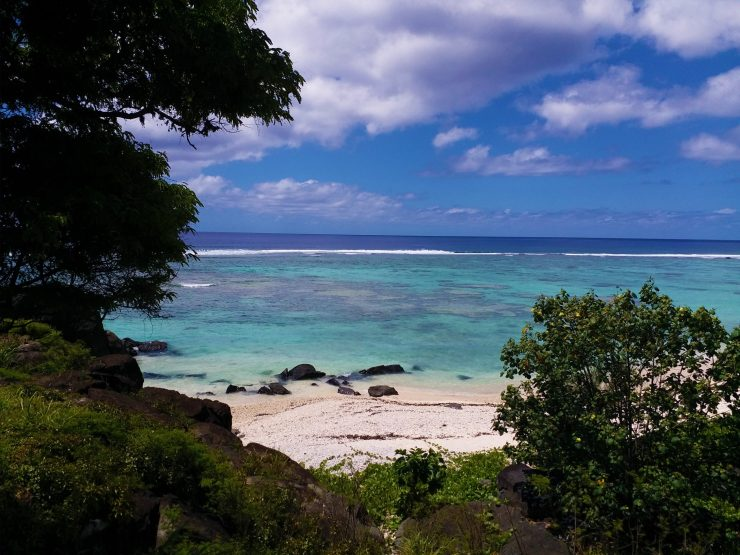K in Motion Travel Blog. The Captivating Cook Islands. Rarotonga Coastal View Through Trees
