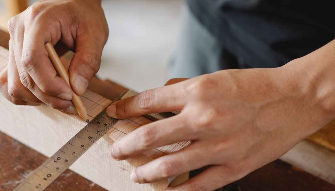 man working with equipment on table in carpentry shop