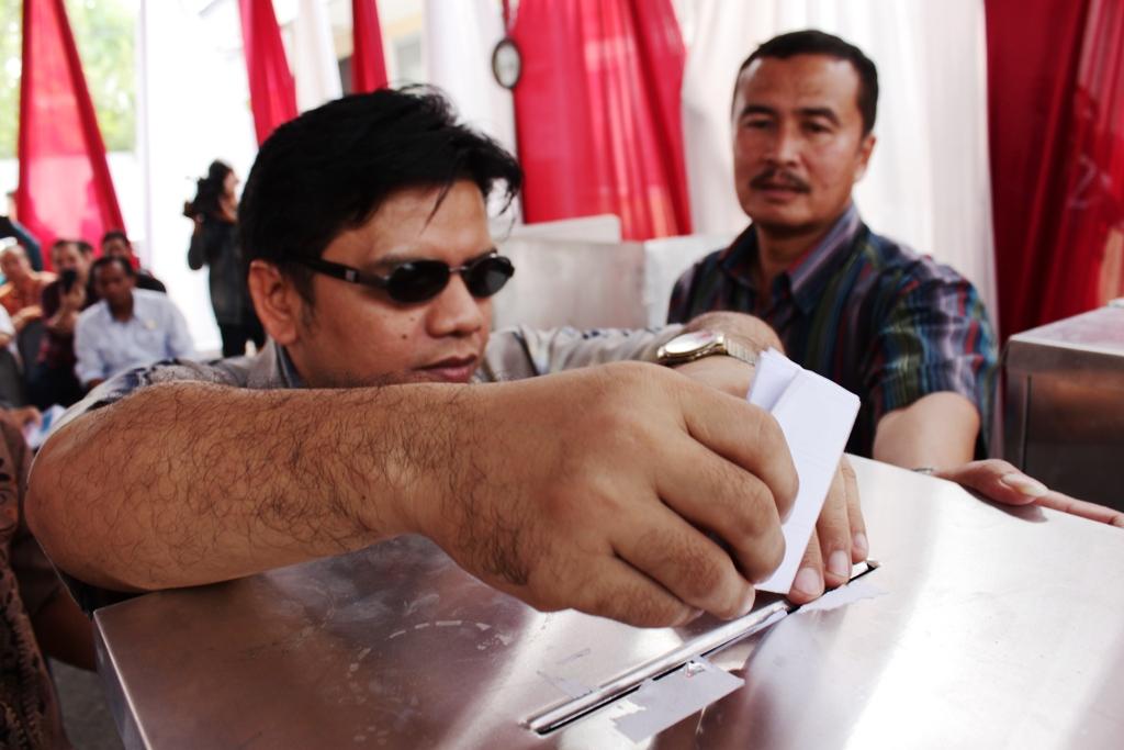 Seorang penyandang tuna netra tengah memasukkan surat suara ke kotak suara saat simulasi pelaksanakan Pileg 2014. FOTO/HP