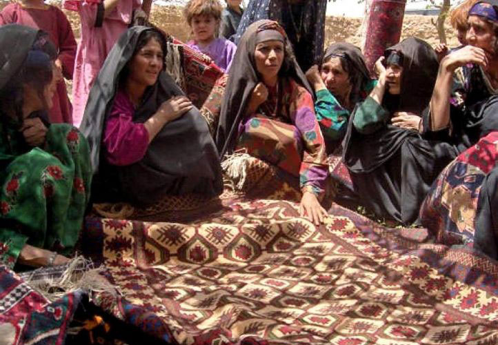 Afghan women selling rugs.