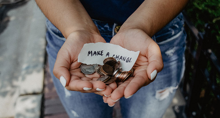 """Two hands holding some coins with a note, """"MAKE A CHANGE."""""""