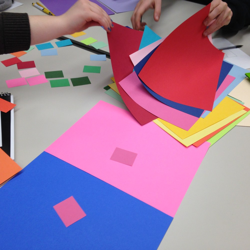 Students experimenting with sheets of paper of various colors.