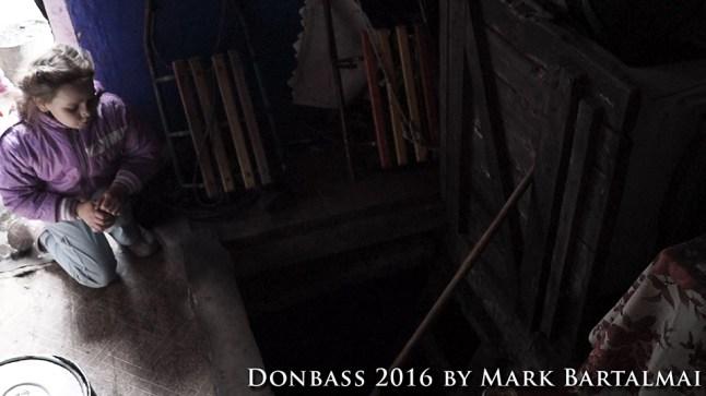 Der Keller ist Lilijas Zufluchtsort mit ihrer Familie, wenn der Beschuss einsetzt. Nur eine Abraumhalde trennt sie von der Frontlinie. / The basement is Lilijas refuge with her family when the shelling starts. Only a slag heap separates them from the frontline.