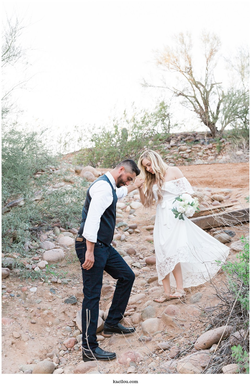 Salt river elopement photo of bride and groom walking down hill