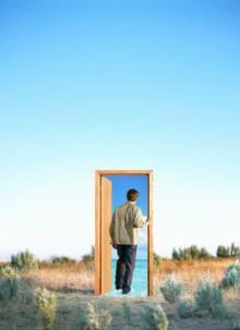 Man walking through doorway with ocean, in desert
