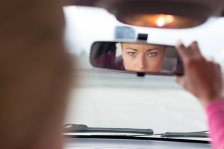 Lady Looking in Rear View Mirror - Lagging Economic Indicators