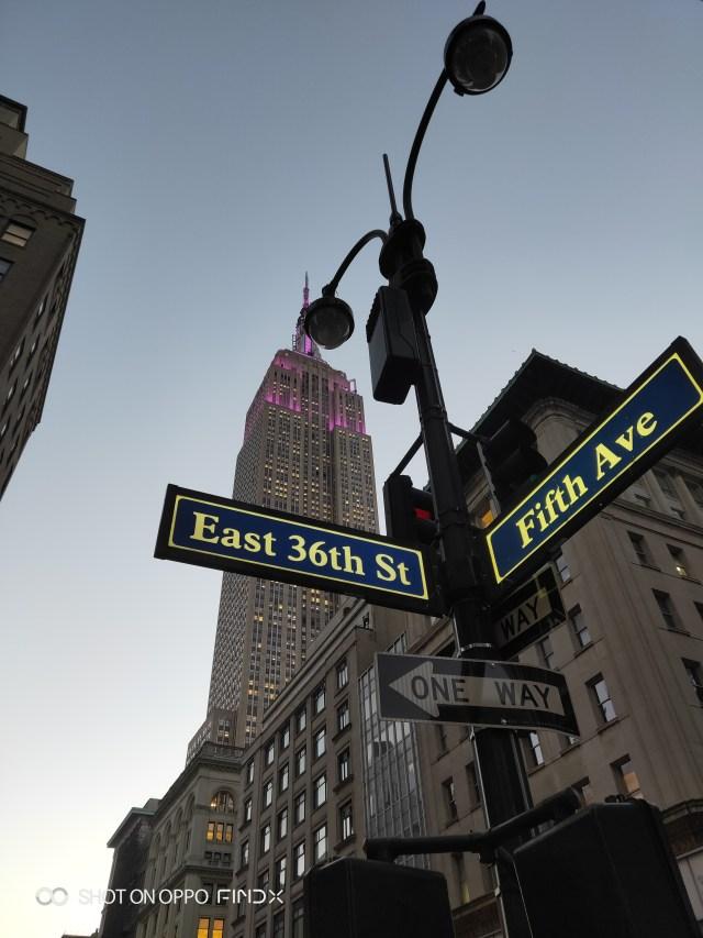 ป้ายบอกชื่อถนน โดยมีตึกเอ็มไพร์สเตทเป็นแบ็กกราวด์ที่ด้านหลัง