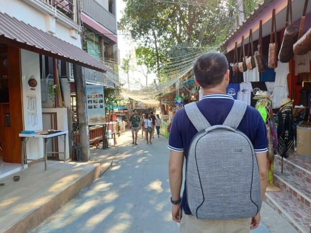 ผู้ชายผมสั้น ใส่เสื้อสีน้ำเงิน สะพายเป้ Cozistyle City Backpack Slim สีเทา กำลังเดินอยู่ในตลาด