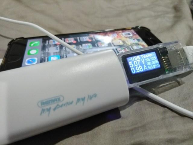 หน้าจออุปกรณ์วัดแรงดันและกระแสไฟฟ้าขณะที่กำลังชาร์จแบตเตอรี่จากพาวเวอร์แบงก์ให้กับ iPhone