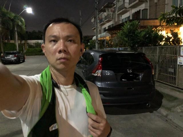 ผู้ชายใส่เสื้อยืดสีขาว และมีผ้าพันคอสีเขียว กำลังยืนอยู่หน้ารถสีเข้มคันนึง ตอนกลางคืน