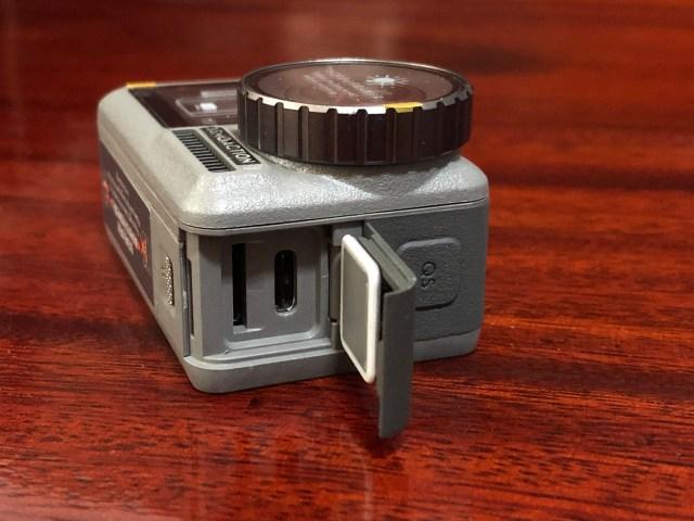 ตัวกล้องด้านขวา ฝาปิดของตัวเครื่องถูกเปิดอยู่ เผยให้เห็นถึงสล็อตใส่ MicroSD card และพอร์ต USB Type-C และมีปุ่ม QS (Quick Switch) อยู่