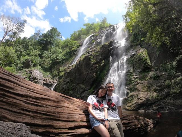ภาพของคู่หนุ่มสาว ใส่เสื้อคู่ กำลังถ่ายภาพอยู่หน้าขอนไม้ใหญ่ หน้าน้ำตกคลองลาน