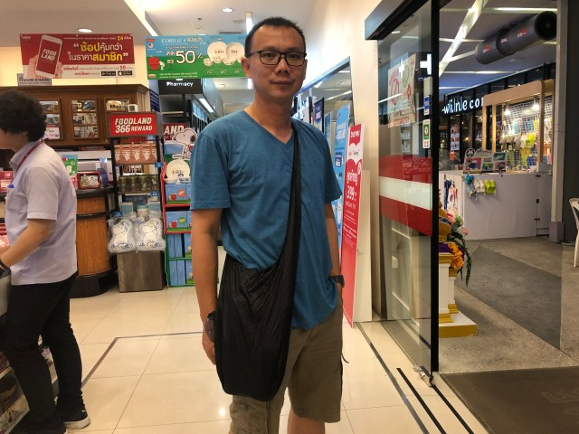 ภาพของตัวผม ใส่เสื้อสีน้ำเงิน สะพายกระเป๋าย่ามสีดำไว้ที่ไหล่ ภายในซูเปอร์มาเก็ต
