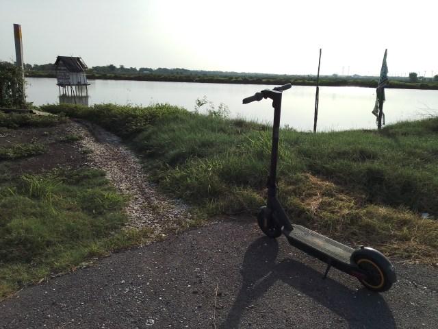 ภาพของสกู๊ตเตอร์ไฟฟ้า Ninebot Kickscooter MAX จอดอยู่ริมบ่อน้ำ ในบ่อหน้ามีบ้านหลังเล็กๆ อยู่หลังนึง