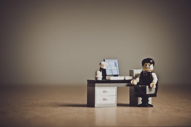 ภาพของตัวต่อ Lego รูปร่างพนักงานออฟฟิศ ทำหน้าตาสิ้นหวัง มีโต๊ะและคอมพิวเตอร์อยู่ข้างๆ