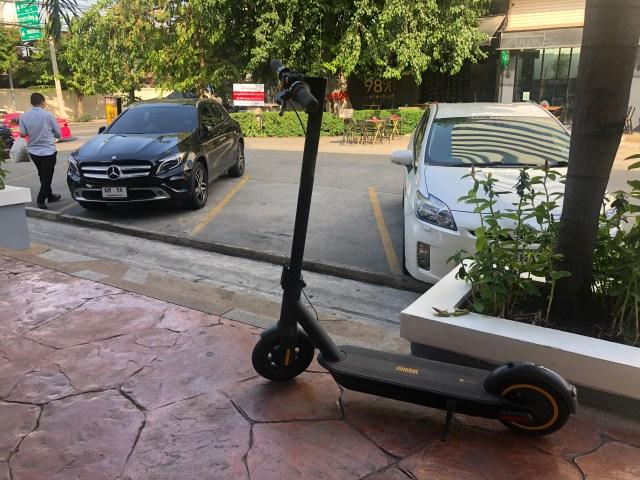 สกู๊ตเตอร์ไฟฟ้า Ninebot Kickscooter MAX จอดตั้งอยู่ตรงทางเดินใกล้ที่จอดรถ