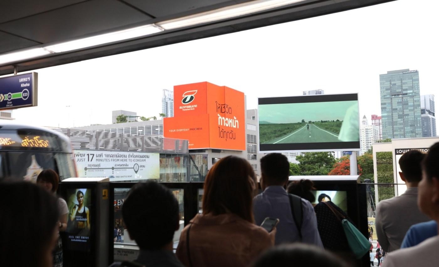 ภาพบนชานชาลารถไฟฟ้า BTS มีโฆษณาของธนาคารธนชาตฉายอยู่บนจอ LED บนตึก