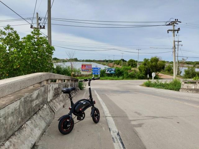 ภาพของจักรยานไฟฟ้า กำลังจอดอยู่ข้างทางบนสะพานข้ามคลอง ด้านหน้าเป็นสามแยก