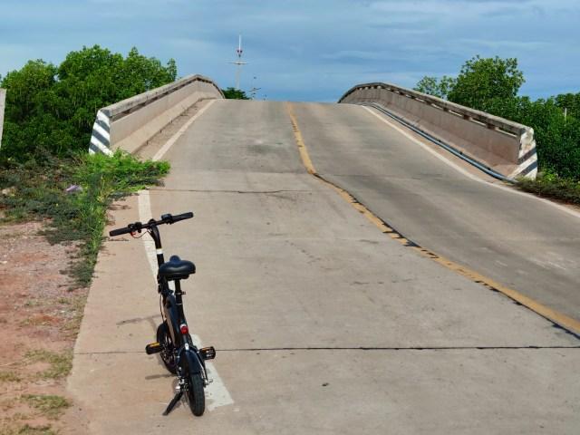 ภาพของจักรยานไฟฟ้าจอดอยู่ริมถนน ด้านหน้าเป็นสะพานข้างคลองสูงๆ