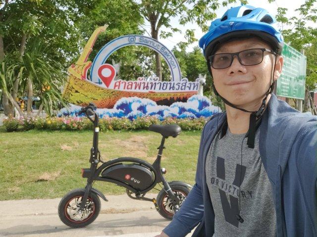 ภาพเซลฟี่ของผม ใส่หมวกกันน็อกสำหรับขี่จักรยานสีฟ้า มีจักรยานไฟฟ้าอยู่ด้านหลัง และมีป้าย ศาลพันท้ายนรสิงห์ อยู่เป็นแบ็กกราวด์