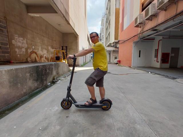 ผมในชุดเสื้อเชิ้ตสีเหลือง กางเกงสีน้ำตาลเข้ม กำลังยืนขี่สกู๊ตเตอร์ไฟฟ้า Ninebot Kickscooter MAX อยู่