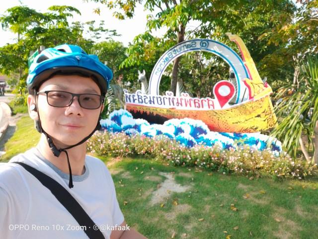 ผมในเสื้อเชิ้ตสีขาว สะพายเป้สีดำ ใส่หมวกกันน็อกจักรยานสีฟ้า ถ่ายรูปหน้าแบ็กดรอปศาลพันท้ายนรสิงห์