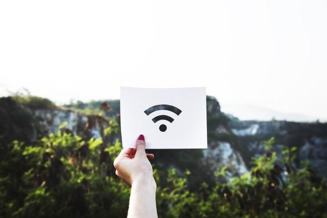 ภาพของมือข้างซ้ายของผู้หญิง ที่กำลังถือกระดาษที่ถูกฉลุเป็นลวดลายสัญลักษณ์ของ WiFi โดยมีภูเขาเป็นแบ็กกราวด์ของภาพ