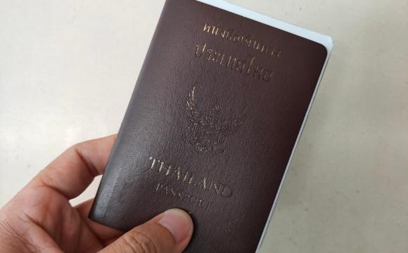 พาสปอร์ตประเทศไทย ปกสีเลือดหมู ด้านในมีกระดาษเอกสารเหน็บไว้อยู่