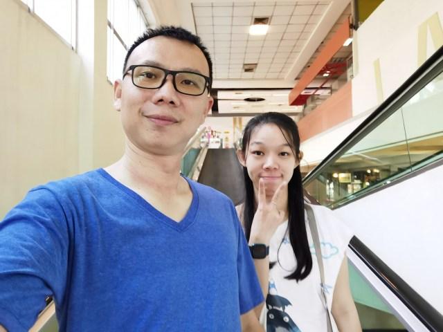 ภาพของผู้ชายผมสั้น ใส่แว่น ใส่เสื้อยืดสีขาว กำลังยิ้มให้กับกล้อง และผู้หญิงผมยาวสีดำ ใส่เสื้อสีขาว ใส่นาฬิกา กำลังยิ้มทำท่าชูสองนิ้ว