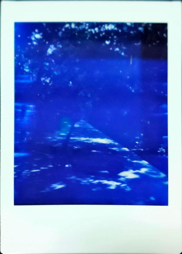 ตัวอย่างภาพถ่ายด้วย Escura Instant 60s เป็นภาพถ่ายสกู๊ตเตอร์ที่จอดอยู่กลางทางเดิน ที่มีต้นไม้เรียงรายสองข้างทาง ภาพแสงน้อย มืดกว่าที่ควรจะเป็น และมีเงาแสงสีฟ้าๆ ด้วย
