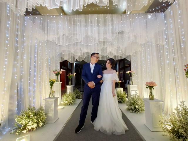 ภาพของเจ้าบ่าวในชุดสูทสีน้ำเงินกับเจ้าสาวกำลังยืนมองหน้ากัน ในซุ้มผ้าสีขาวที่ประดับไปด้วยไฟ LED