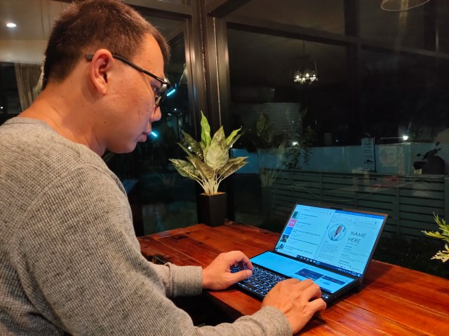 ตัวผมเอง ใส่เสื้อแขนยาวสีเทา กำลังนั่งใช้งาน ASUS ZenBook Duo อยู่บนโต๊ะไม้