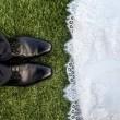 ภาพของเท้าเจ้าบ่าวในกางเกงและรองเท้าหนังสีดำ กับชายกระโปรงชุดเจ้าสาวสีขาวของเจ้าสาว
