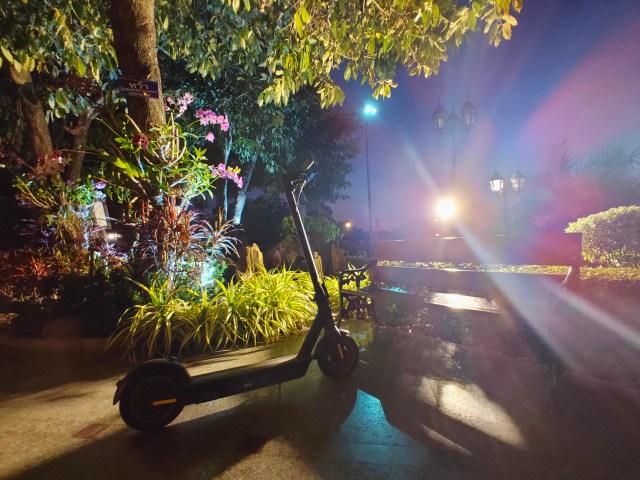 สกู๊ตเตอร์ไฟฟ้า Ninebot Kickscooter MAX จอดในสวน ถ่ายย้อนแสงไฟ