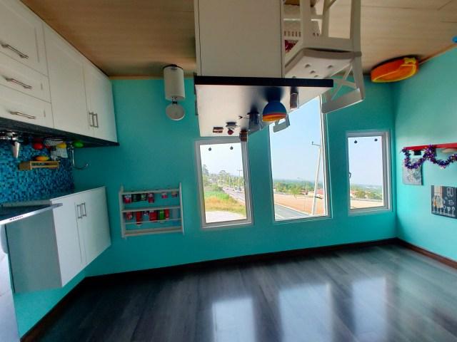 ภาพห้องครัวที่สิ่งต่างๆ ไม่ว่าจะเป็นโต๊ะทำครัว อ่างล้างจาน ตู้เก็บของ ถูกจัดวางแบบกลับหัวทั้งหมด แต่มองออกไปนอกหน้าต่าง ถนนและวิวไม่ได้กลับหัว