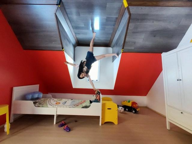 ภาพห้องนอนเด็ก อยู่ใต้หลังคา ผนังสีแดง มีตู้เสื้อผ้าสีขาว มีผู้หญิงคนนึงกำลังยืนกลับหัวอยู่